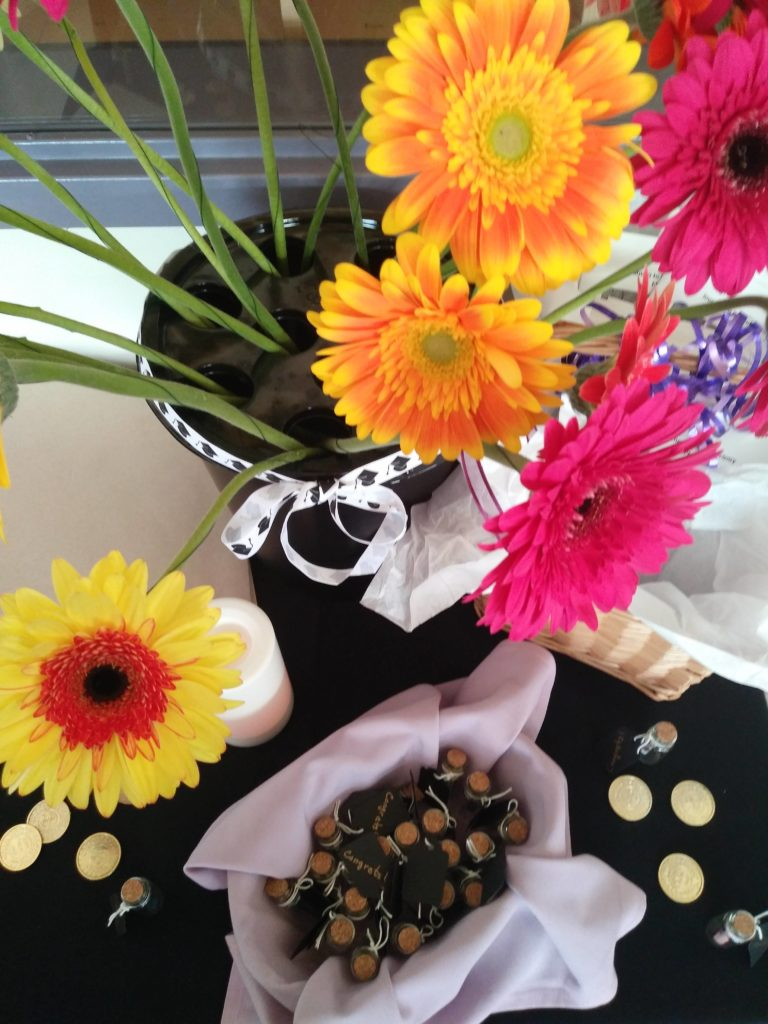 a vase of bright cosmos on a dark tablecloth surrounded by coins to represent abundance.