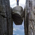 A participant standing on top of a boulder on a dream trip to Norway.