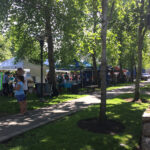 picture of a park with tents set up and people milling about
